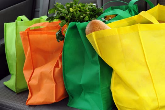 Four reusable grocery bags next to each other with groceries inside